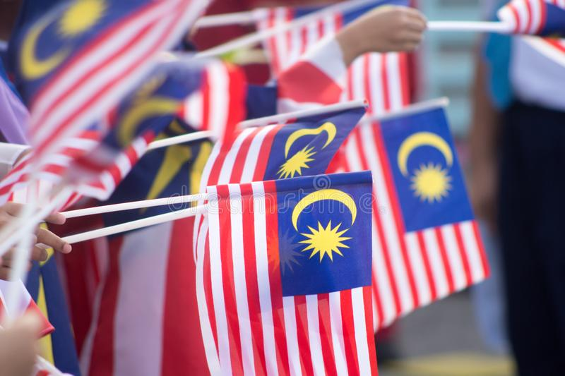 Hand waving Malaysia flag also known as Jalur Gemilang in conjunction with the Independence Day celebration or Merdeka Day. Hand waving Malaysia flag also known stock photo