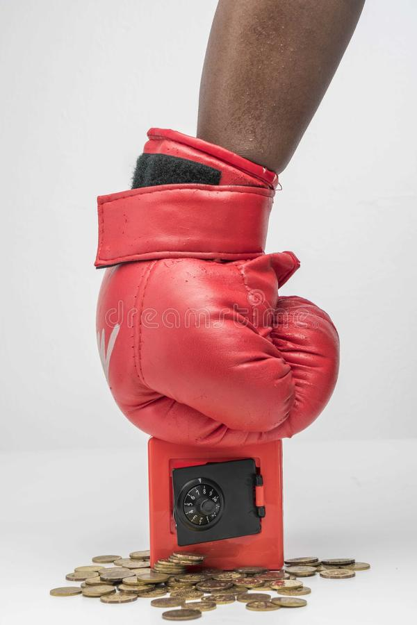Hand wearing boxing glove and punch the red safe box stock photos