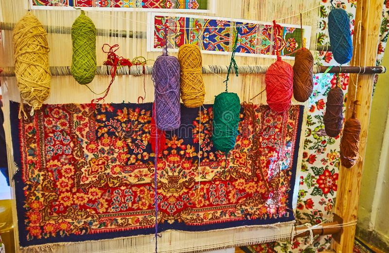 Hand weaving loom, Mahan, Iran. Hand weaving loom with examples of colored woolen yarns and traditional Persian carpet, covered with fine floral pattern, Mahan stock images