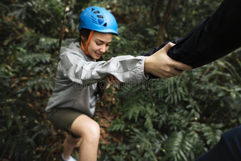 Hand, welche beim Wandern die oben helfende Frau hält lizenzfreie stockfotos