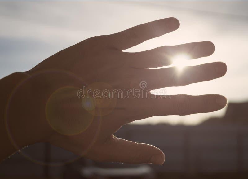 Hand, welche die Sonne mit grellem Glanz undeutlich macht stockfotos