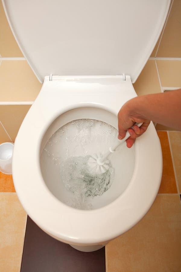 Hand, welche die Toilette wäscht lizenzfreies stockbild