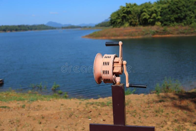 Hand In werking gestelde Sirene bij rivier stock fotografie