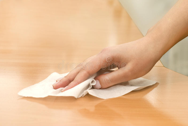 Hand with wet wipe. Cleaning table