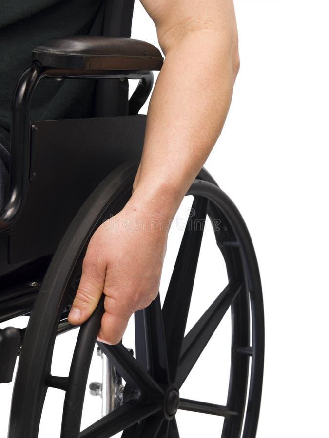 Hand on wheel chair stock photography