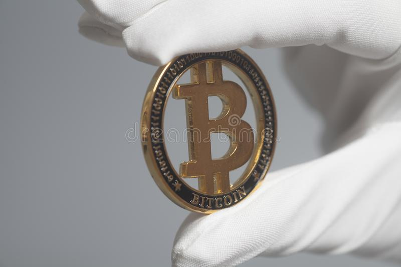 Hand in White Glove holds Golden Bitcoin Crypto Currency .Mining concept. royalty free stock photography