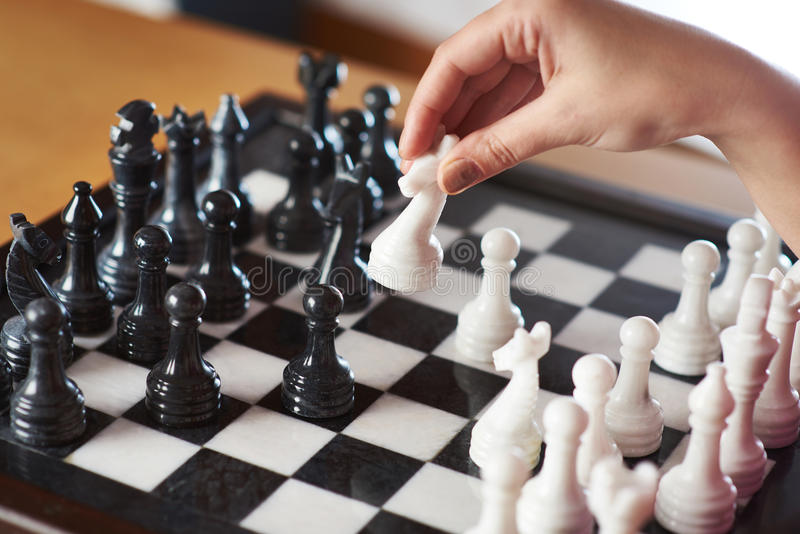 Hand with white knight makes a move. Closeup stock photo