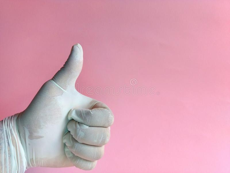Hand with white latex glove holding thumb up on pink background. medical concept stock photos