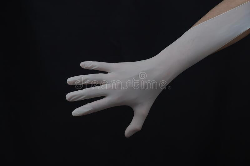 Hand in white medical glove on a black background. gesturing hand in protective glove stock photography