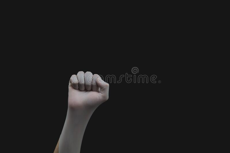 Hand in white medical glove is clenched into a fist. gesturing hand in protective glove on a black background stock images