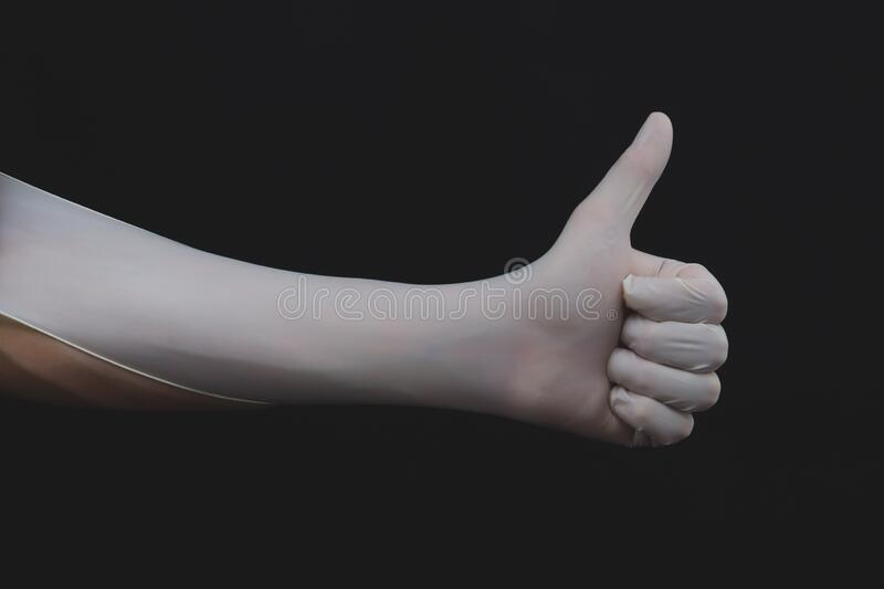 Hand in white medical glove shows thumbs up royalty free stock image
