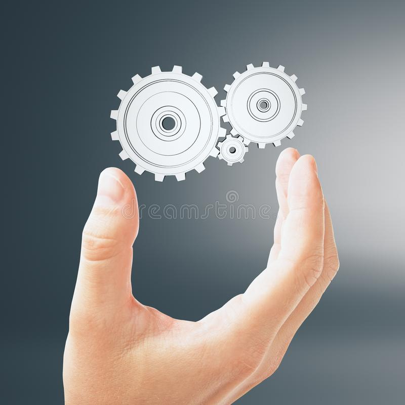 Business idea concept. Hand and white painted cogwheel at grey background. 3D render royalty free stock photography