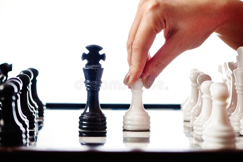 Hand with white pawn moves to black king. Closeup stock photography