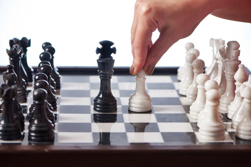 Hand with white pawn moves to black king. Closeup stock image