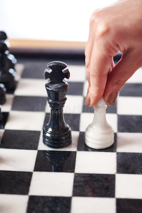 Hand with white pawn moves to black king. Closeup royalty free stock photo