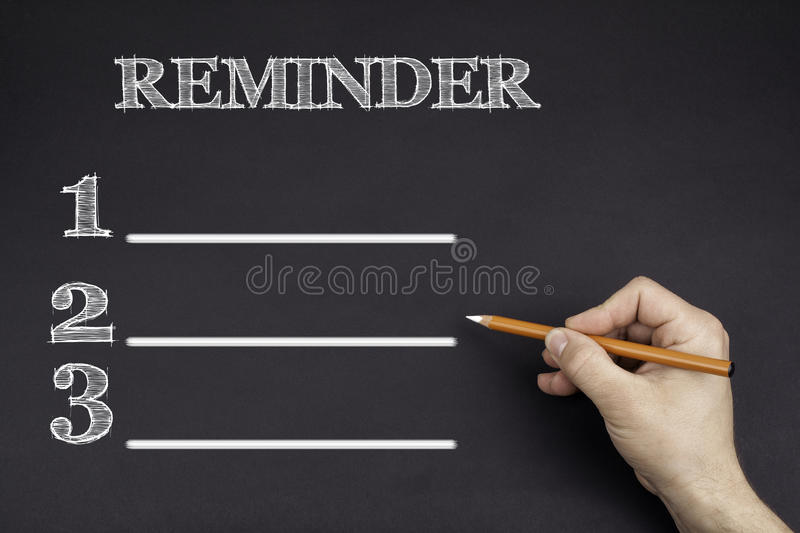 Hand with a white pencil writing: Reminder blank list royalty free stock photos