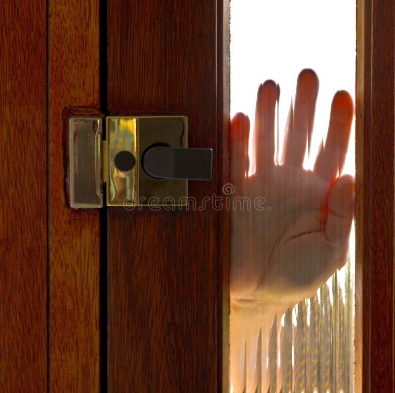 Hand on window in door stock images
