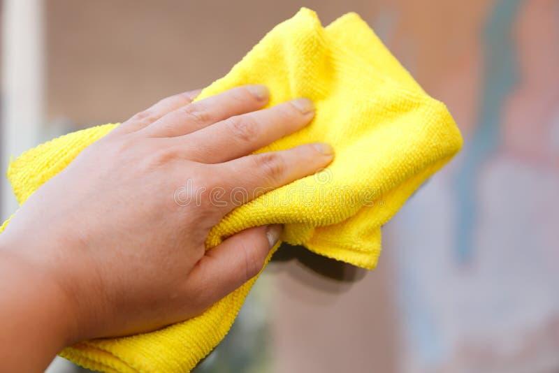 Hand wischt eine Schicht Staub ab Säubern von Voraussetzungen lizenzfreies stockbild