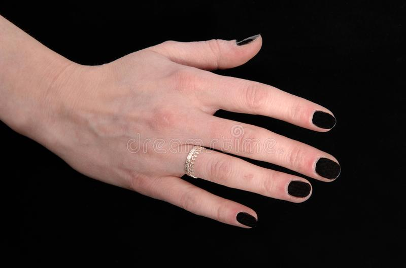 The hand of a woman on black background. A close up image of the hand of a young woman with her black finger nails and a ring, isolated for black background stock photography