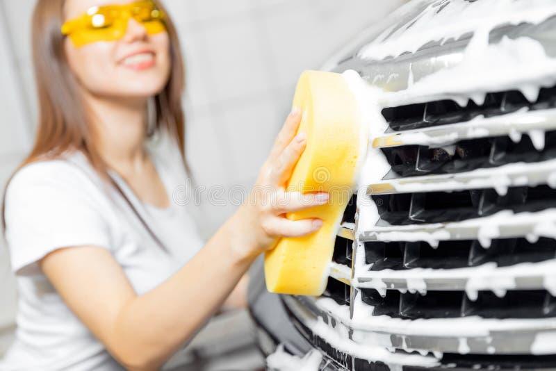 Hand woman car wash foam with yellow sponge headlights.  stock photo