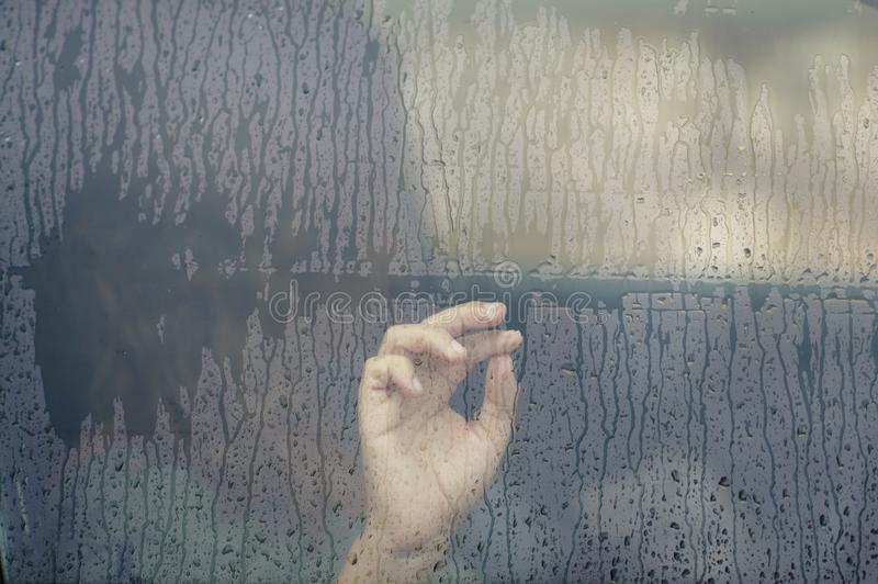 Hand of woman in the car window with rain drop. Loneliness and depression concept. stock photos