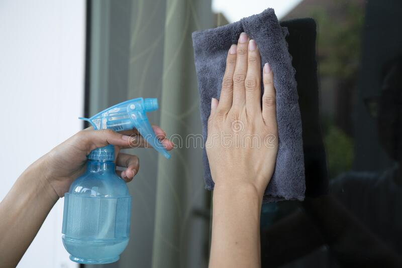 Hand of woman cleaning with cleanser spray into the mirror window at home royalty free stock image