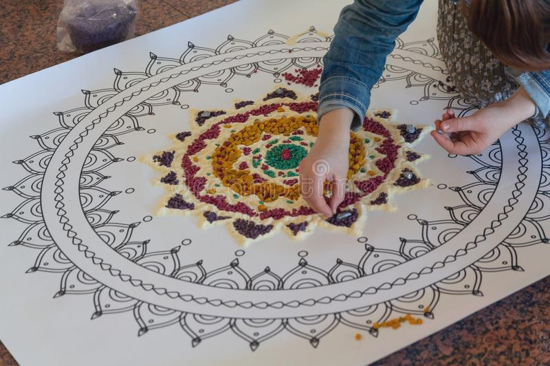 Hand of the woman creating a mandala. By means of color sand royalty free stock photos