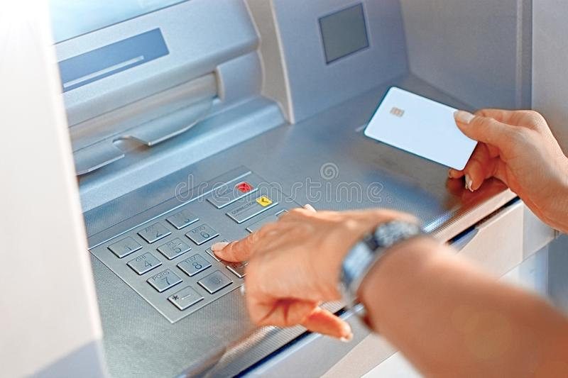 Hand of a woman with a credit card, using an ATM. Woman using an ATM machine with her credit card. royalty free stock photo