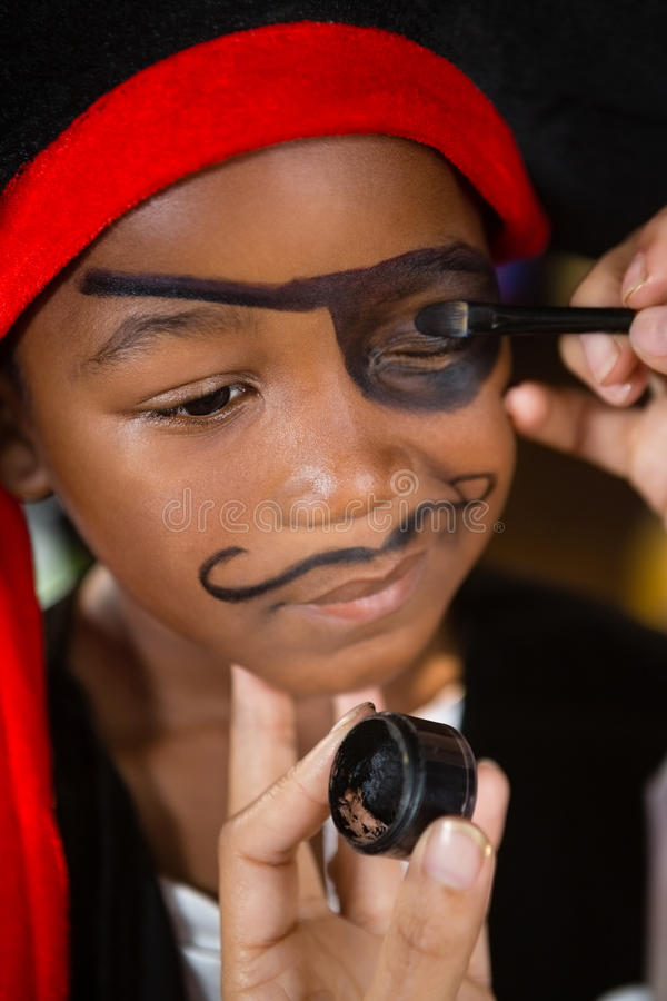 Hand of woman drawing on boy eyes. At home stock photo