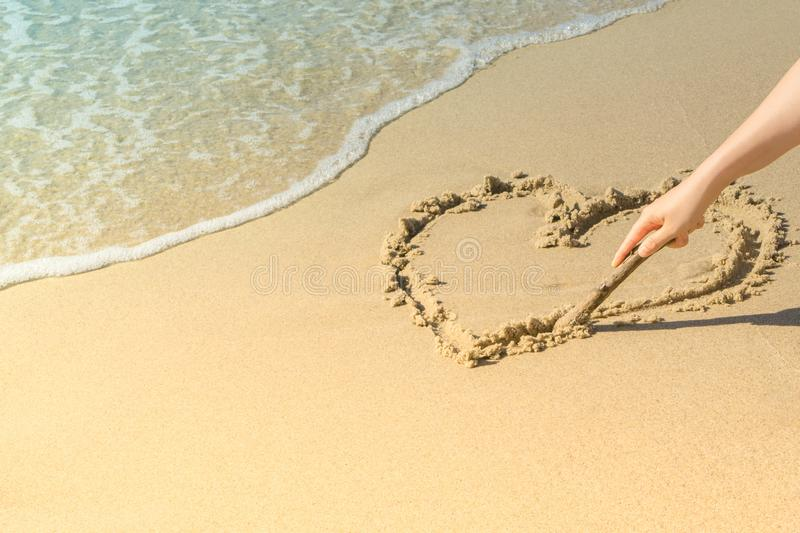 Hand of woman drawing heart on sand in beach near sea wave. Copy space royalty free stock photos