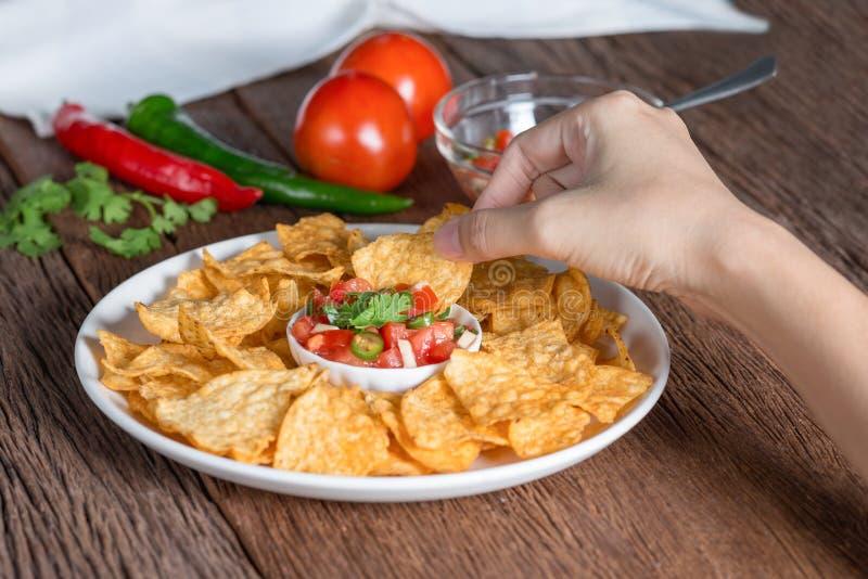 Hand of woman eating tortilla chips dip tomato salsa. stock photos