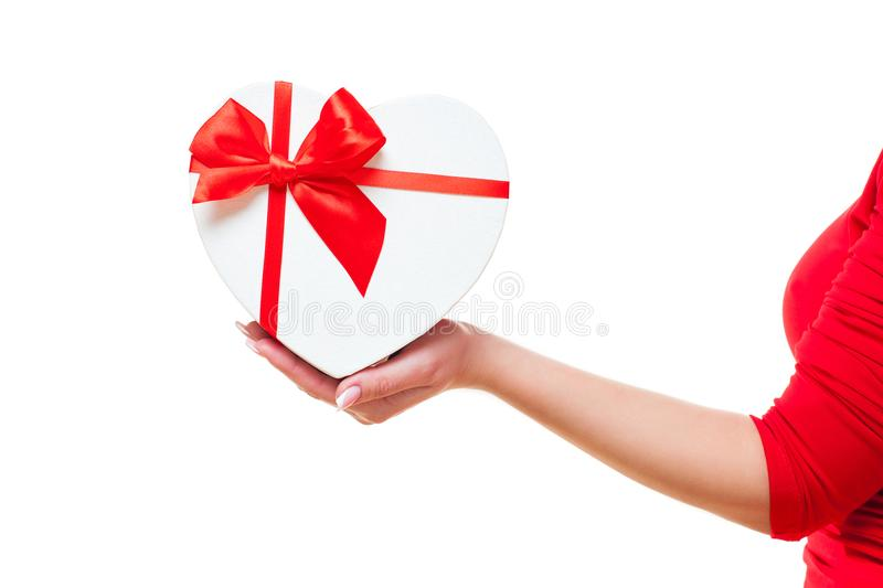Hand of a woman and with gift box red heart-shaped, isolated on white background. valentines day theme. royalty free stock photos