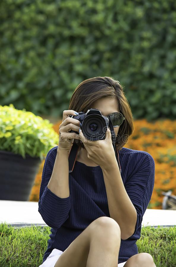 Hand woman holding the camera Taking pictures Background of trees and flowers stock image