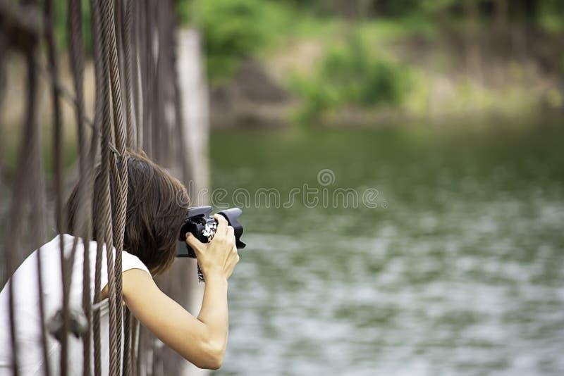 Hand woman holding the camera Taking pictures on wooden bridge Background Kaeng Krachan dam phetchaburi , Thailand stock images