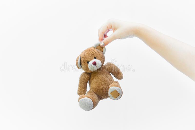 Hand woman holding ear brown teddy bear toy on white. Background stock images