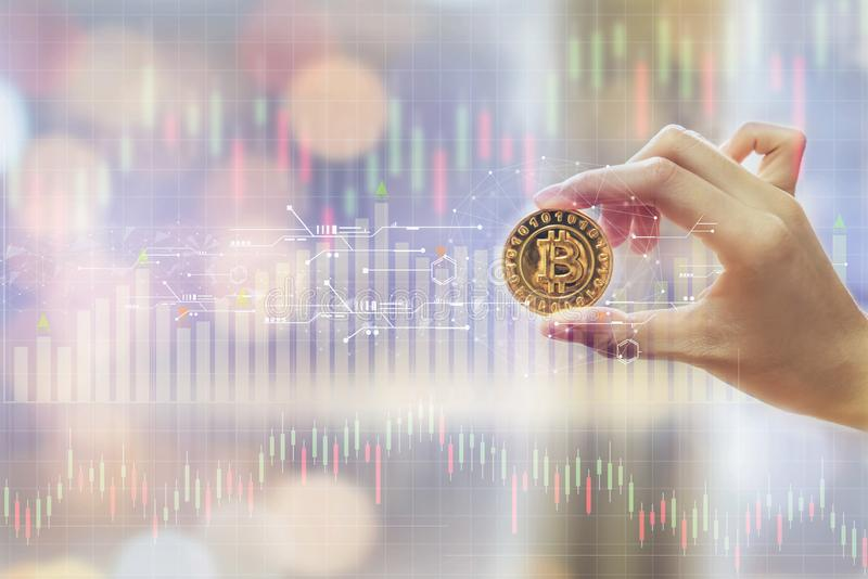 Hand of woman holding a Gold Bitcoin is digital currency, and show graph with the stock exchange trading graph for background. royalty free stock images