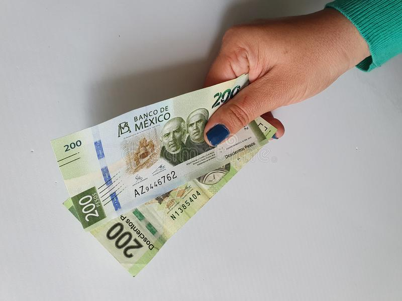 Hand of a woman holding mexican banknotes of 200 pesos royalty free stock image