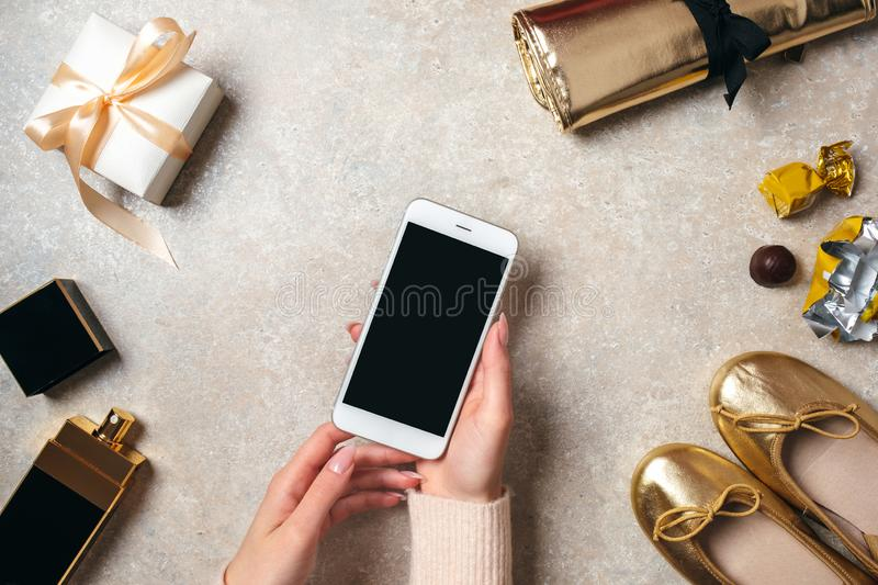 Hand of woman holding mobile phone with black screen over feminine table with fashionable stuff. Home workspace desk with beauty stock photo