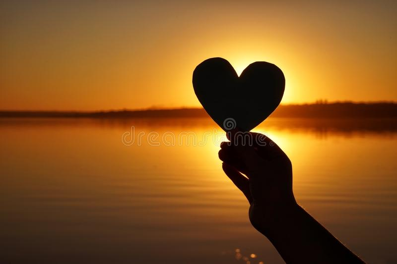 Hand of woman holding paper heart outdoors at sunset royalty free stock images