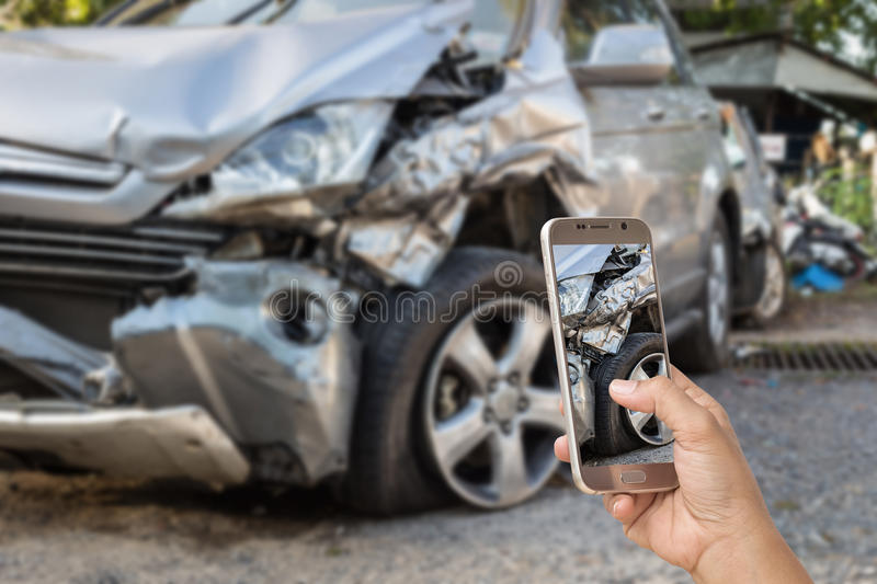 Hand of woman holding smartphone and take photo of car accident. Close up hand of woman holding smartphone and take photo of car accident royalty free stock photography