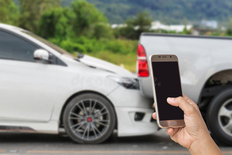Hand of woman holding smartphone and take photo of car accident stock image