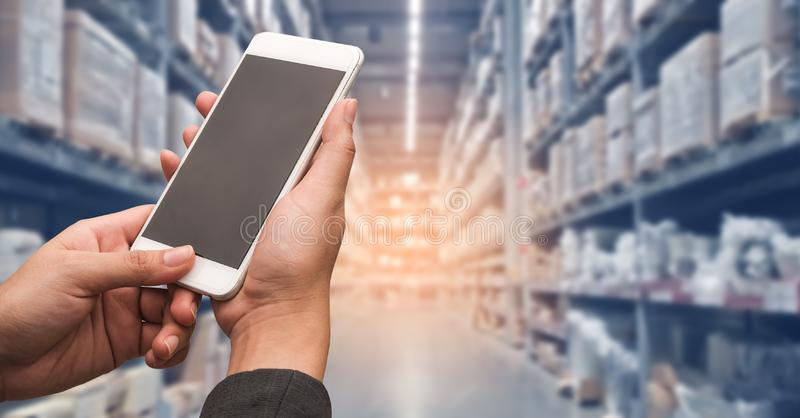 Hand woman holding smartphone to shopping online with blur storage background.  royalty free stock image