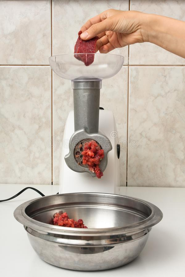 Hand making forcemeat with meat grinder royalty free stock photos