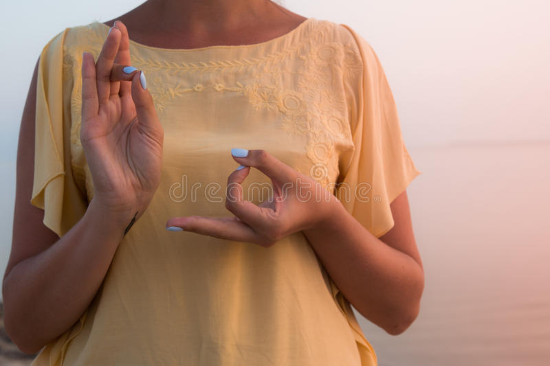 Hand of a woman meditating in a yoga pose on the beach at sunset stock photography