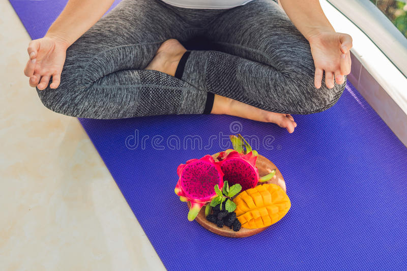 Hand of a woman meditating in a yoga pose, sitting in lotus with fruits in front of her dragon fruit, mango and mulberry royalty free stock images