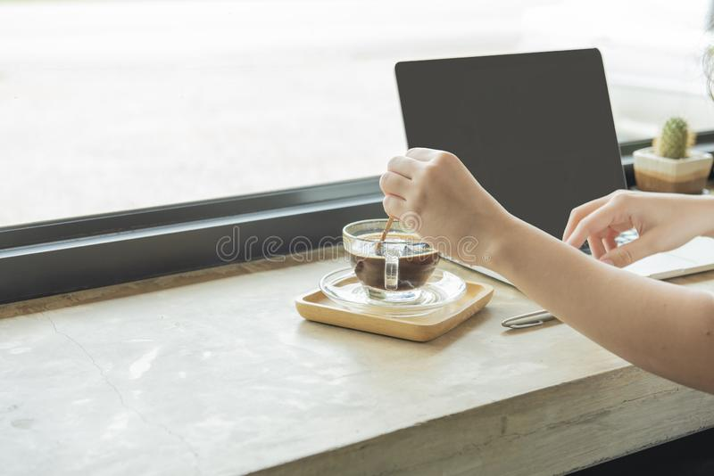 Hand of woman mix cup of hot black coffee while using laptop.E-commerce, university education, internet technology, or startup royalty free stock photo