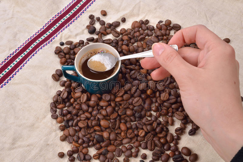 Hand of woman mixing the sugar in a green cup of coffee. Roast. Hand of a woman mixing the sugar in a green cup of coffee. Roasted coffee beans on jute royalty free stock images