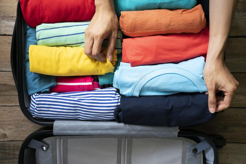 Hand of woman packing a luggage for a new journey and travel for a long weekend royalty free stock photos