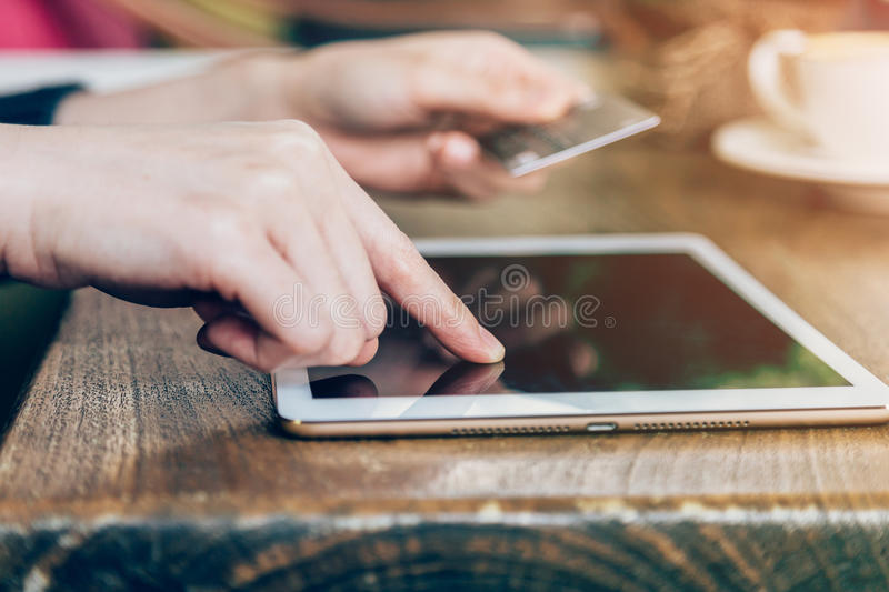 Hand woman pays by credit card for online purchase on a tablet royalty free stock photos