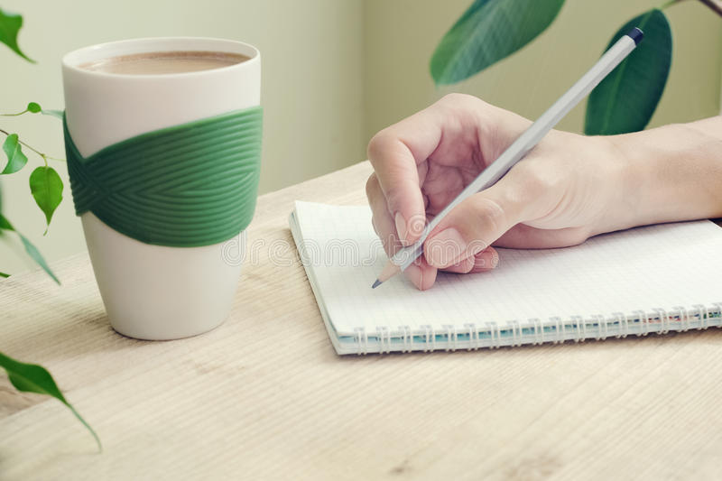 The hand of a woman with pencil is written in diary with spirals. Beside to the table is cup of coffee and plant with green leaves stock photography